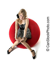 Blonde girl, who sits in a red chair