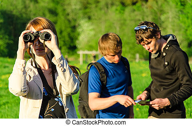 Three friends traveling Girl looking through binoculars