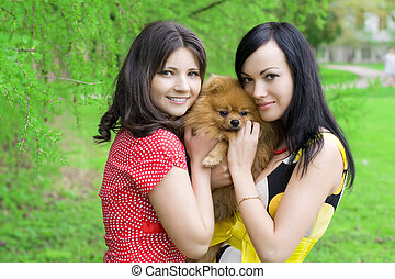 Girls with a dog in the park - Image of two girls with a dog...