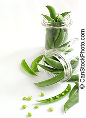 Snow peas pods in jar on the white background