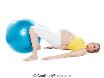 Pregnant woman doing relaxation exercise - A young pregnant...