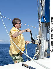 Raising the sail - Crew member of a sailboat is raising the...