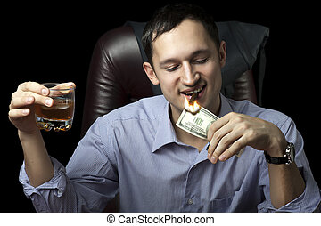Young handsome man lighting his cigar with $100 note