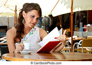 Young woman is sitting in the cafe - Young brunette woman is...