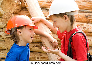 young workers work - two little workers building at the...
