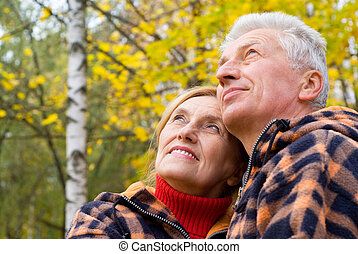 old couple at nature - cute old couple posing in autumn park