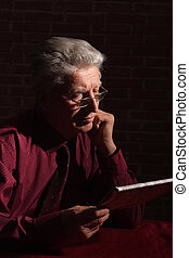 old man with newspaper in dark - old man with newspaper in...