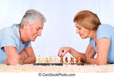 old couple playing chess - cute old couple playing chess on...