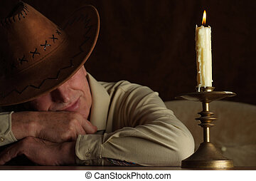 Handsome caucasian man sits at a table with a candle on a...