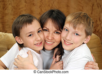 A beautiful Caucasian mama with two adorable brothers on a...