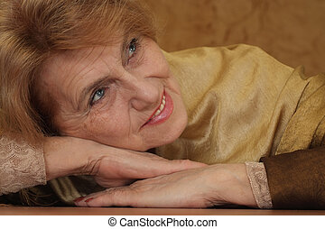 elderly woman sitting on a sofa on a brown background