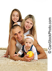 good family of four people lying on the carpet