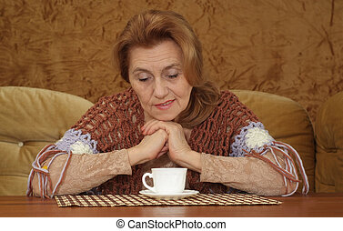 aged woman sitting on a sofa on a brown background
