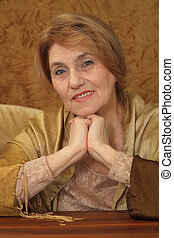 beautiful old woman sitting on a sofa on a brown background