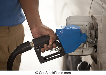 refilling the car with a gas pump - close-up of a mens hand...