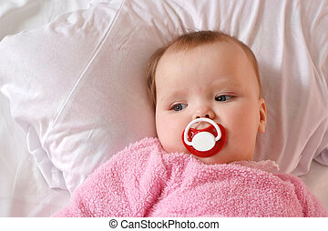 Little girl with a charming pacifier lying on the bed