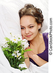 A beautiful caucasian bliss girl in bed with a bouquet of flowers on a light background