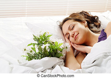 A beautiful caucasian girl in bed with a bouquet of flowers