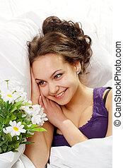 A beautiful caucasian smile girl in bed with a bouquet of flowers on a light background