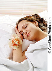 A beautiful caucasian girl with a flower in a bed