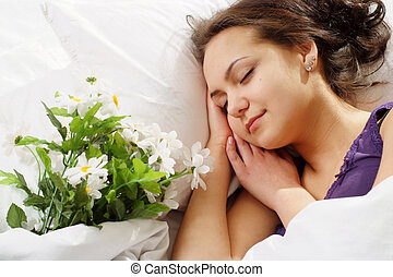 A beautiful caucasian nice girl in bed with a bouquet of flowers on a light background