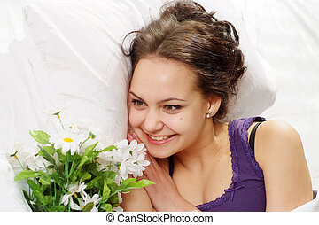 A beautiful caucasian luck girl in bed with a bouquet of flowers on a light background