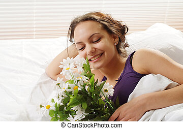 A beautiful caucasian female in bed with a bouquet of flowers