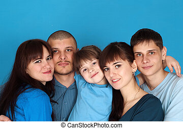 Caucasian beautiful good family consisting of five people together on a blue background