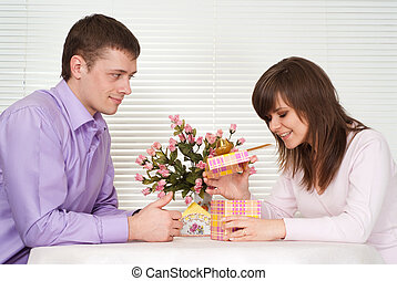 Joy Caucasian guy and his girlfriend are sitting at a table