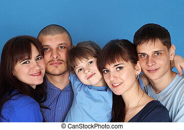 Caucasian beautiful nice family consisting of five people together on a blue background