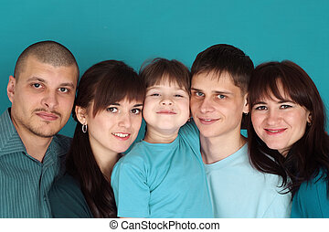 Caucasian beautiful happy family consisting of five people together on a turquoise background