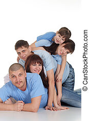 Caucasian beautiful family consisting of five people lying on the floor of the pyramid on a white background