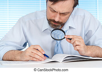 A business man is considering a magnifying glass on a light...