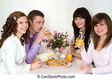 Good Caucasian group of four people with pizza and juice sitting in a cafe