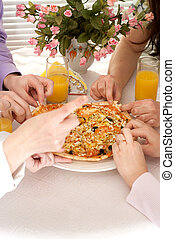 Caucasian group of four people with pizza and juice sitting