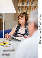Old woman reading newspaper with husband in library -...