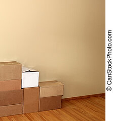 Moving Boxes - Stacks of moving boxes against a blank wall.