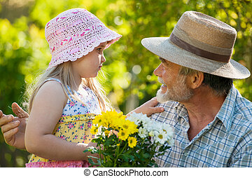 Gardening - Happy grandfather with his granddaughter in the...