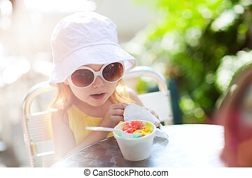 Cute girl eating ice cream - Outdoor portrait of adorable...