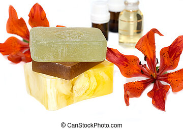 soap with natural ingredients , flowers an bottles of aromatic oil