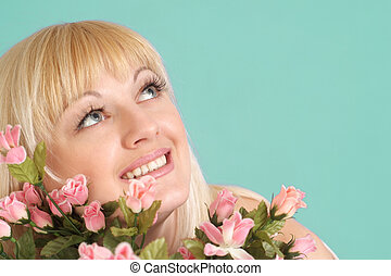 Portrait of a beautiful blonde Caucasian smile lady with flowers on a light background