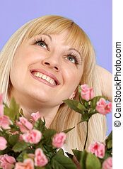 Portrait of a beautiful blonde Caucasian good lady with flowers