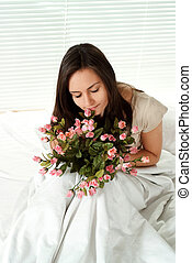 Young Caucasian girl sitting in bed with flowers
