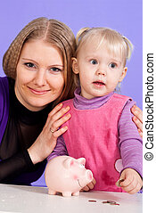 Pretty Caucasian mama with her daughter play with the piggy...