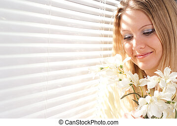 Beautiful Caucasian woman standing in the morning with a bouquet of flowers on a light background
