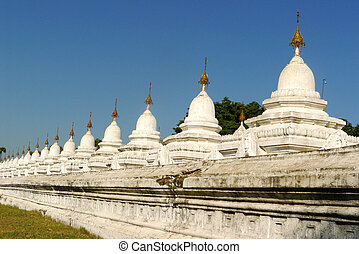 Buddhist towers in Myanmar - Row of historic white buddhist...