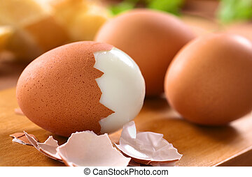 Hard Boiled Eggs - Fresh hard boiled eggs with shell beside...