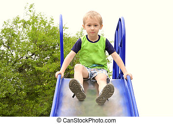 Boy Child playing in Park playground with tree on background