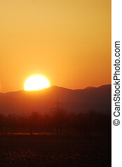 burning sun - very bright sun at sunset with mountain and...