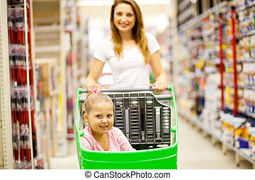 walking in shopping mall aisle - mother and daughter walking...